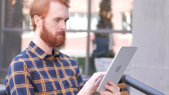 Thumbnail for Beard Young Man Using Tablet while Sitting Outdoor