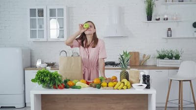 Pretty woman standing in kitchen. Young woman playing with fruits in the kitchen