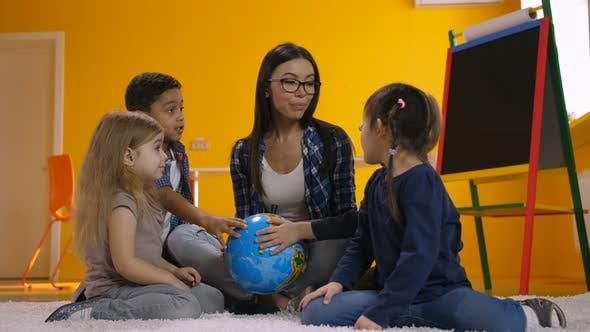 Teacher and Kids Discussing Globe in Kindergarten