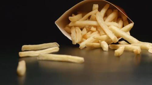 Box with french fries falls on a table