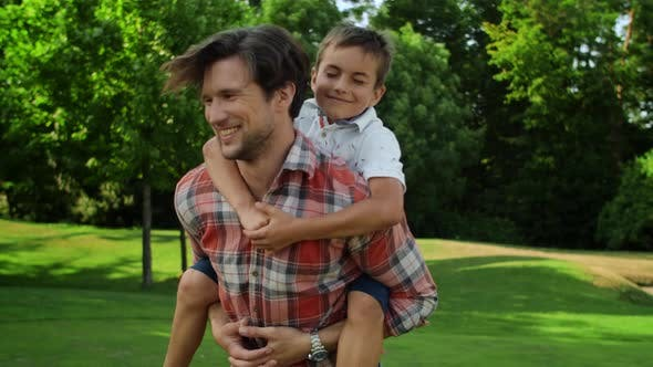 Thumbnail for Father Spinning Around in Park with Son on Back. Funny Family Having Fun Outside