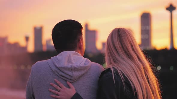 Thumbnail for View From the Back of a Young Girl with Blond Hair Hugging an Asian Guy on the Background