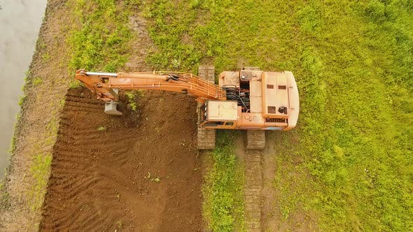 Thumbnail for Excavator Digging a Trench in the field.Aerial Video.