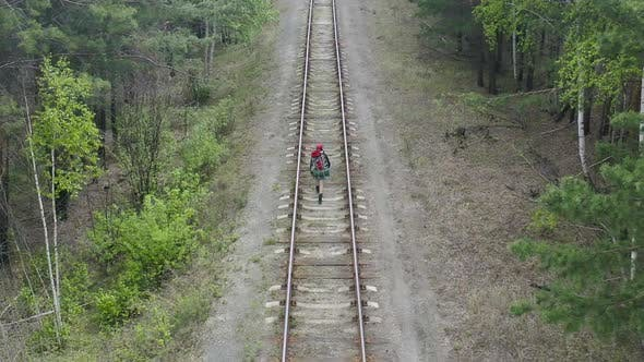 Cover Image for Woman with Backpack Walking in a Forest Along Railway Road - Aerial View.