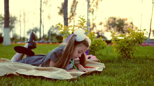 School Girl Painting Lying on the Lawn