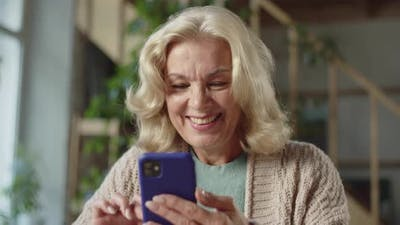 An Old Woman Looks at Photographs on the Phone