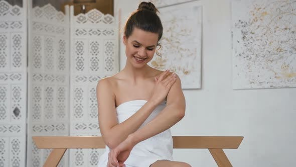Thumbnail for Attracttive Young Woman Applying Cream on Her Skin in the Spa Salon