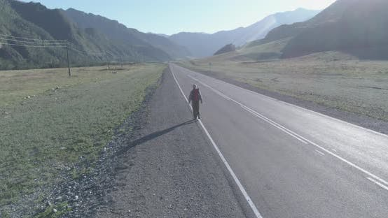 Thumbnail for Flight Over Hitchhiker Tourist Walking on Asphalt Road. Huge Rural Valley at Summer Day