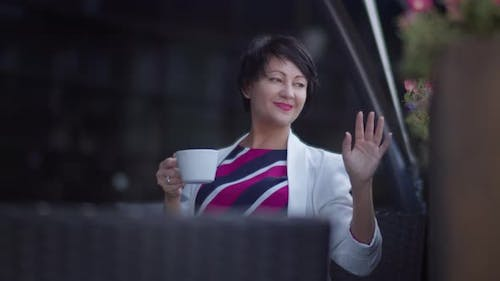 Happy Woman Sits in a Cafe with a Cup of Coffee and Greets Her Friends on the Street