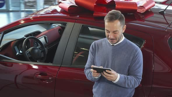 Thumbnail for A Smiling Man Is Standing By the Car and Typing in the Phone