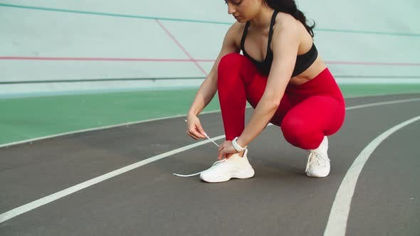 Thumbnail for Woman Runner Preparing for Workout on Track, Fitness Girl Tying Up Shoes Outdoor