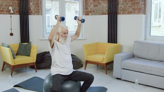 Mature Man in Sportswear Sitting on Fitball and Doing Exercises with Dumbbells