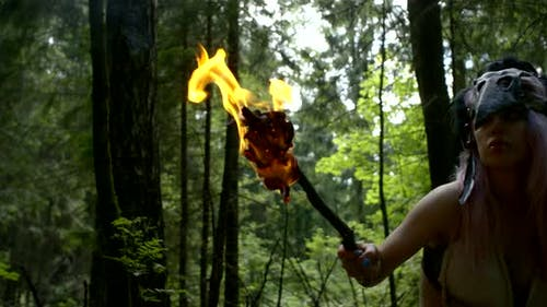Savage Woman Is Looking Around and Hearing in Forest in Daytime, Burning Torch