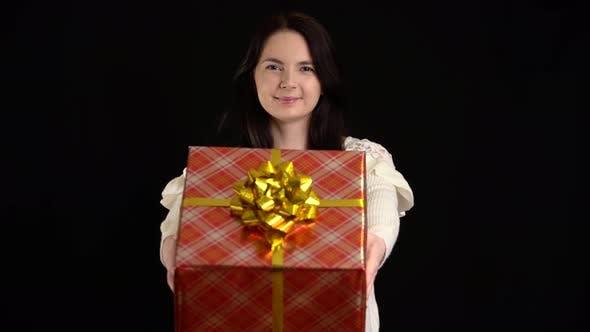 Junge Frau gibt eine Geschenkbox auf schwarzem Hintergrund. Geschenkbox mit weißem Band für ein glückliches neues Jahr