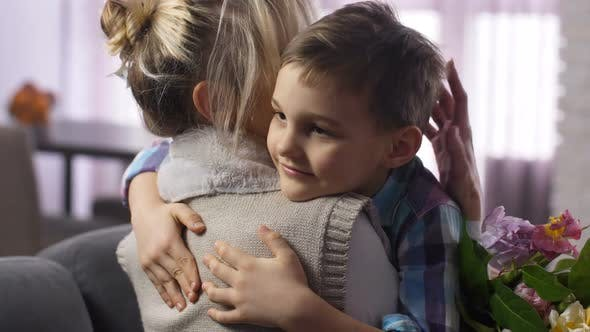 Cover Image for Closeup Cute Boy Felicitating and Hugging Mother