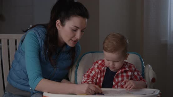 Thumbnail for Portrait of Little Boy Learning With Beautiful Mother To Draw With Colored Pencils shot on RED