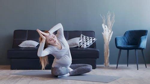 Young Pregnant Girl Practicing Prenatal Yoga at Home