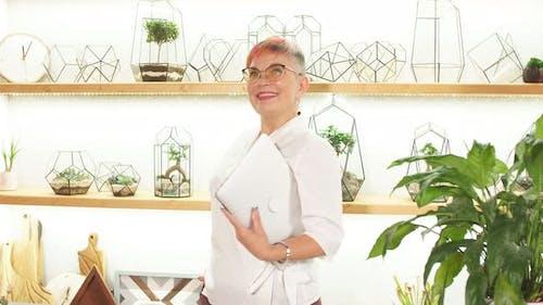 Modern Woman Florist in White Bathrobe Talking on Mobile Phone, Showing Thumb, Good News