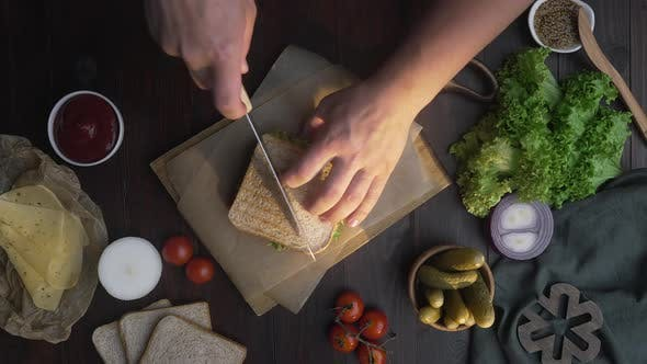 Thumbnail for Man Cuts Club Sandwich in a Half By Sharp Knife on a Wooden Board at the Kitchen