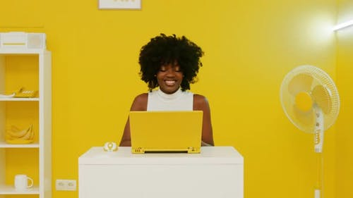 Happy Black Woman Is Using Laptop In Yellow Room
