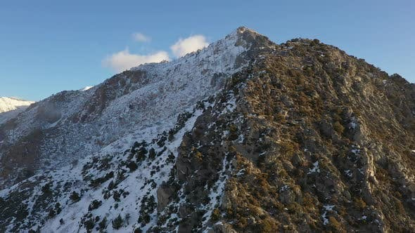 Thumbnail for View of mountain with snow on the shady side as sun melts the sunny side