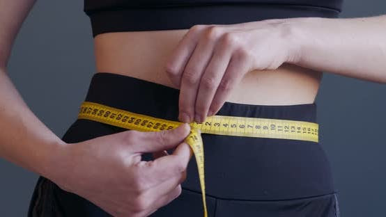 Cover Image for Sporty Woman Measuring Size of Her Waist, Close Up