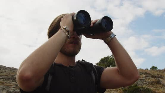 Young boy looks at the landscape with binoculars in the mountains
