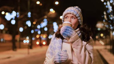 Happy Woman with Coffee and Shopping Bag in Winter