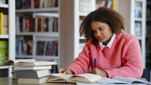 African American Female Student Studying in Library