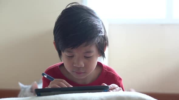 Asian Child Drawing Picture With Digital Pen On Tablet Pc Computer