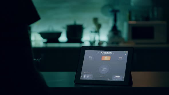 Man Looking at Tablet with Wireless Lighting Automation Software