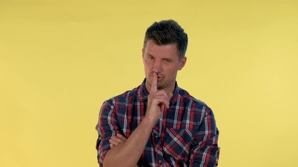 Thumbnail for Close Up of Young Man Making a Hush Gesture on Yellow Background.