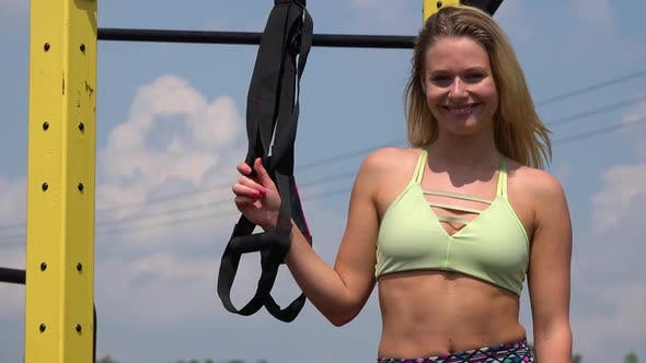 Thumbnail for A Fit Beautiful Woman Stands By Gym Ropes at an Outdoor Gym and Smiles at the Camera - Closeup