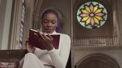 Young African-American Woman Reading Bible in Christian Church
