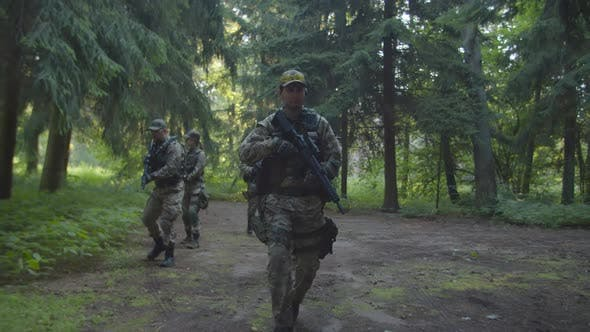 Detachment Commander Giving Arm Signal to Soldier in Forest at Dawn