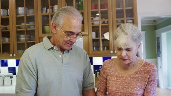 Thumbnail for Senior man feeding wife in kitchen