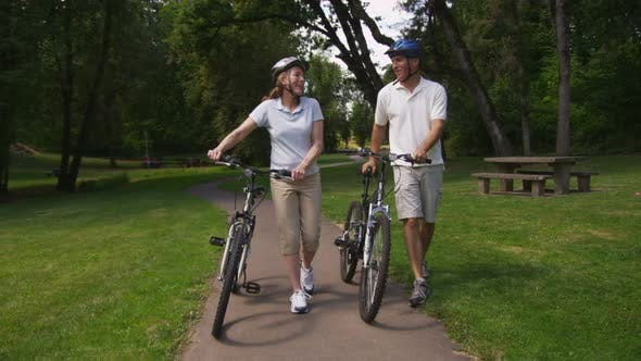 Thumbnail for Mature couple walking with bicycles, slow motion