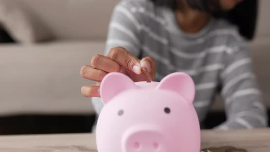 Hand girl putting coins into piggy bank