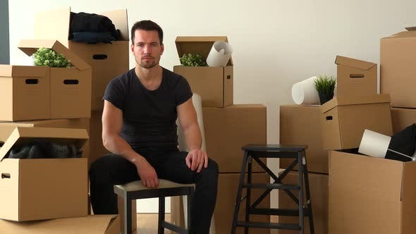 Thumbnail for A Moving Man Sits on a Chair and Looks Seriously at the Camera in an Empty Apartment