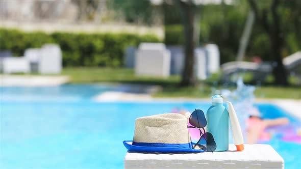 Suncream, Hat, Sunglasses Near Swimming Pool