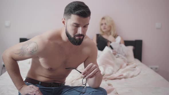 Thumbnail for Close-up Portrait of Young Bearded Caucasian Man with Tattoo on Shoulder Sitting on Bed, Taking Off