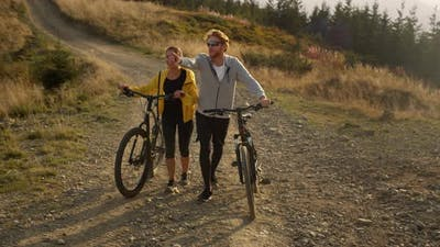 Man and Woman Walking on Path with Bicycles