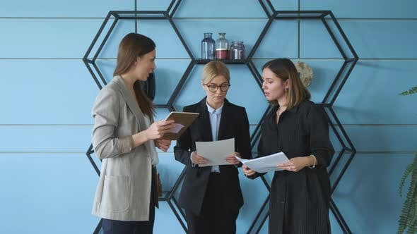 Three women stand against the wall in the office and check documents for a business project