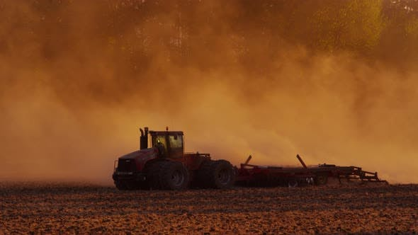 Thumbnail for Tractor plowing field at sunset.