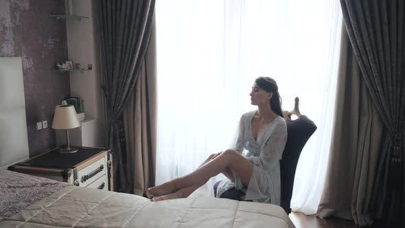 Thumbnail for Morning Shot of Sexy Young European Bride in Blue Peignoir and Lingerie Sitting on Chair and