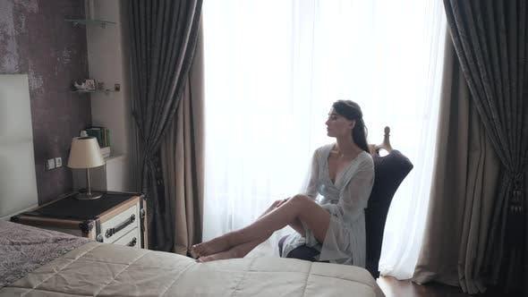 Thumbnail for Morning Shot von Sexy junge europäische Braut in Blau Peignoir und Dessous sitzen auf Stuhl und