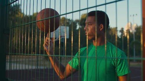 Geschickter Athlet Spinning Basketball auf Finger