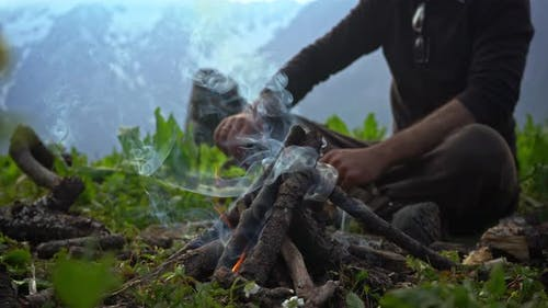 A Person Putting Some Tree Branches On A Campfire During Cold Morning - Close Up