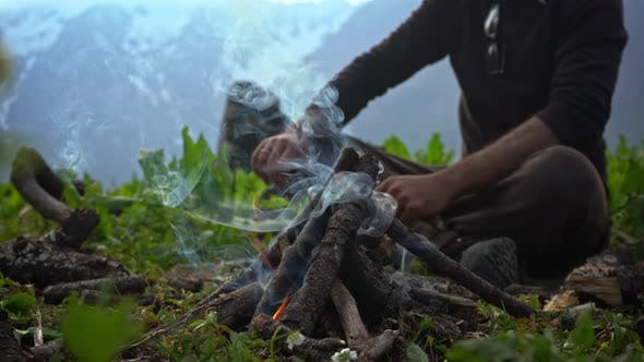 Thumbnail for A Person Putting Some Tree Branches On A Campfire During Cold Morning - Close Up