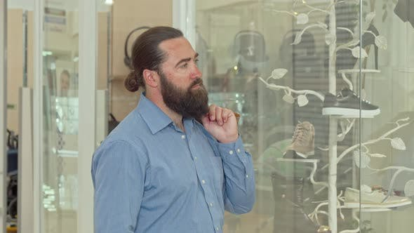 Thumbnail for Mature Bearded Man Looking Thoughtfully at the Display of Clothing Store